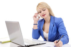 Attractive blonde secretary sitting at her desk, on phone Royalty Free Stock Images