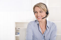 Attractive blonde senior businesswoman with headphone. Royalty Free Stock Image
