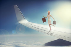 Attractive blonde with shopping bags on the plane wing Stock Photos