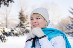 An attractive blonde during a short rest with a smile. An attractive blonde with a chin on her arms with ski poles during a short rest with a smile looks at the Stock Image