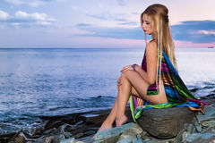 Attractive blonde is sitting on the beach at  sunset Stock Photo