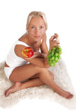 Attractive blonde sitting on fell with fruits. Portrait of sexy girl sitting on fell with grapes and apple in hands Stock Images