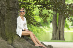 Attractive blonde sitting on the roots of a large tree. Stock Photography