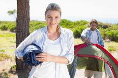 Attractive blonde smiling at camera while partner pitches tent Stock Images