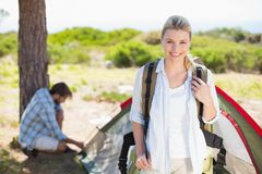 Attractive blonde smiling at camera while partner pitches tent Royalty Free Stock Images