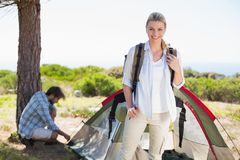 Attractive blonde smiling at camera while partner pitches tent Stock Photo