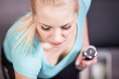 Attractive blonde sports girl lifting dumbbell Stock Image