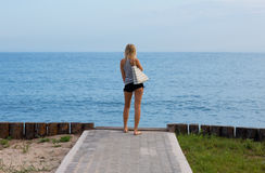 Attractive blonde standing on the beach stock photo