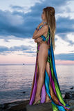 Attractive blonde is standing undressing on the beach at  sunset Royalty Free Stock Photo