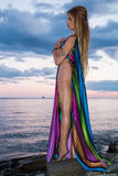 Attractive blonde is standing undressing on the beach at  sunset Royalty Free Stock Photos
