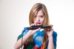 Attractive blonde straighten hair with iron Stock Image