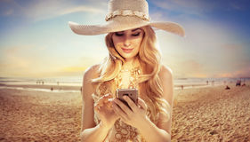 Attractive blonde texing on sunny beach. Attractive blond woman texing on sunny beach Royalty Free Stock Images