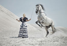 Attractive blonde training the horse Stock Image