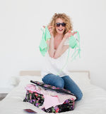 Attractive blonde trying to close her suitcase Royalty Free Stock Photos