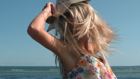 Attractive blonde turning with straw hat on beach Royalty Free Stock Photos