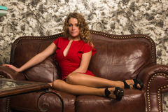 Attractive blonde in the vintage interior. Attractive blonde sitting on the couch  in the vintage interior Royalty Free Stock Photo