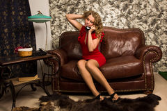 Attractive blonde in the vintage interior. Attractive blonde sitting on the couch  in the vintage interior Royalty Free Stock Photos