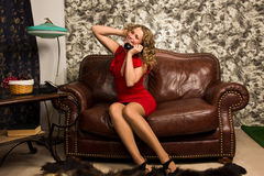 Attractive blonde in the vintage interior. Attractive blonde sitting on the couch  in the vintage interior Royalty Free Stock Images