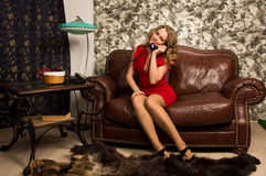 Attractive blonde in the vintage interior. Attractive blonde sitting on the couch  in the vintage interior Stock Photography