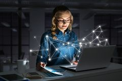 Attractive blonde wearing glasses in dark office using laptop. Mixed media. Smiling beautiful girl looking in glowing laptop screen. 3d rendering Royalty Free Stock Images