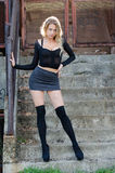 Attractive blonde wearing sexy mini skirt. Long black socks high heels, facing the camera, full length and vertical photo Royalty Free Stock Image
