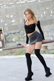 Attractive blonde wearing sexy mini skirt. Long black socks high heels leaning on railing parking bar, facing the camera, full length and vertical photo Royalty Free Stock Images