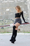 Attractive blonde wearing sexy mini skirt. Long black socks high heels sitting on railing bar parking, facing the camera, full length and vertical photo Stock Photography