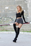 Attractive blonde wearing sexy mini skirt. Long black socks high heels sitting on railing bar parking, facing the camera, full length and vertical photo Royalty Free Stock Images