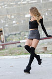 Attractive blonde wearing sexy mini skirt. Long black socks high heels sitting on railing parking bar, looking away, full length and vertical photo Stock Images