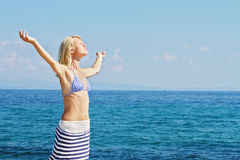 Attractive Blonde Woman  Breathing Happy With Raised Arms, freedom concept, sea, sun, summer, hodiday, vacation. Stock Photo