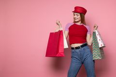 Attractive blonde woman in casual clothes and red hat with colorful shopping bags royalty free stock photos