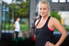 Attractive blonde woman at crossfit gym. Fit young girl rests after workout at a crossfit fitness center. People workout in the background Royalty Free Stock Photography