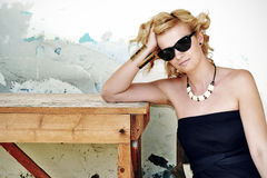 Attractive blonde woman with curly hear and dark sunglasses sitting by the wooden table. Royalty Free Stock Photography