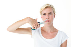 Attractive blonde woman cutting cigarette with scissors. On white background Royalty Free Stock Image