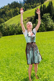 Attractive blonde woman in a dirndl is full of joy Stock Photography