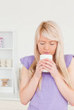 Attractive blonde woman drinking hot drink Stock Images