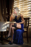 Attractive blonde woman in elegant long dress sitting near a table in a luxurious classic interior. Gorgeous blonde model. Showing her long legs in black Stock Image