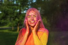 Attractive blonde woman having fun with colorful dry paint at the park. Concept for festival Holi. Attractive blonde girl having fun with colorful dry paint at stock photos