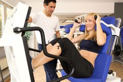 Attractive blonde woman and her trainer in a gym Stock Photography