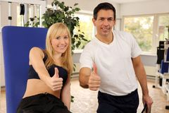 Attractive blonde woman and her trainer in a gym Royalty Free Stock Photo