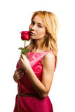 Attractive blonde woman holding a flower Royalty Free Stock Image