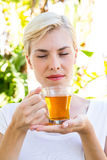 Attractive blonde woman holding glass of tea Royalty Free Stock Image