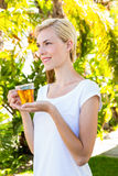 Attractive blonde woman holding glass of tea Stock Images