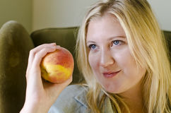 Attractive blonde woman holding peach Stock Photography