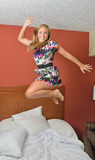 Attractive blonde woman jumping on bed Stock Image