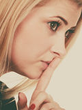 Attractive blonde woman making silence gesture Stock Images