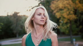 Attractive blonde woman in park on sunset and turning head, her hair is waving. Young smiling woman in nature. Slow mo. stock footage