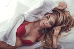 Attractive blonde woman posing in bed Royalty Free Stock Photo
