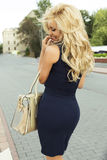 Attractive blonde woman posing. Fashionable beautiful blonde woman posing outdoor. Smiling girl stock photos