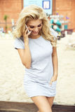 Attractive blonde woman posing. Young fashionable beautiful blonde woman posing outdoor in casual clothes. Girl with long curly hair royalty free stock photography